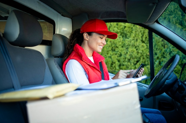 Женский курьер проверяет посылки на цифровом планшете перед доставкой.