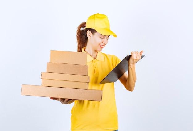 Corriere femminile che consegna uno stock di scatole di cartone e controlla l'elenco dei clienti e degli indirizzi.