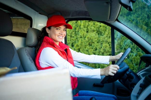 Женщина-курьер за рулем фургона с посылками на переднем сиденье быстро доставляет посылки вовремя.