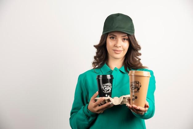 Corriere femminile in uniforme verde che tiene le tazze di caffè.