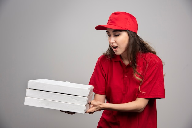 Corriere femmina di presa di scatole per pizza sul muro grigio.