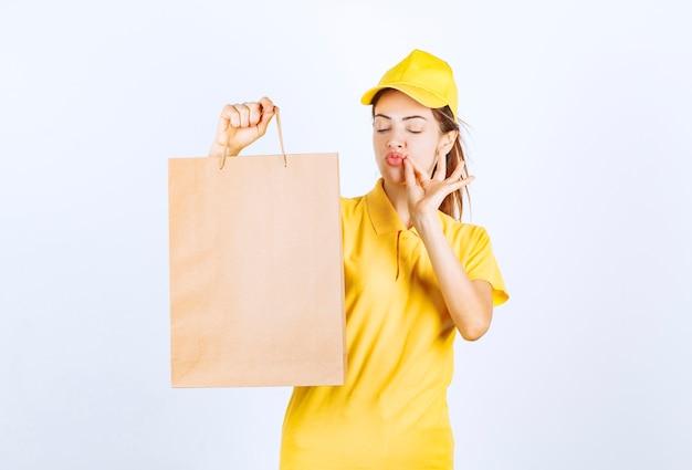 段ボールの買い物袋を持って、楽しみのサインを示す女性の宅配便。