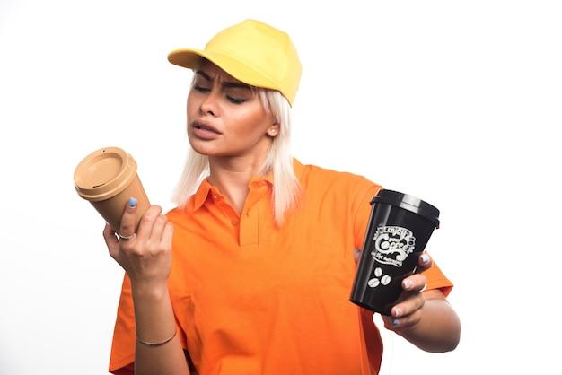 Женский курьер холдинг и глядя на две чашки кофе на белом фоне. фото высокого качества