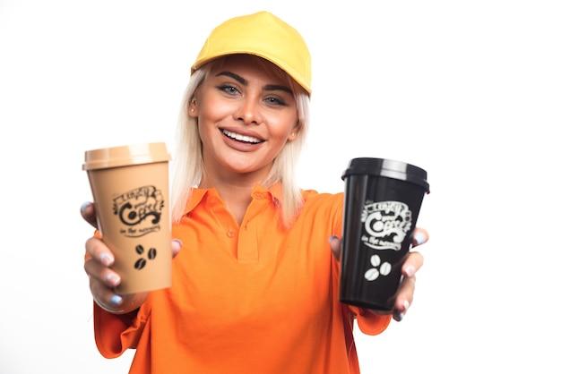 Женский курьер держит и показывает две чашки кофе на белом фоне. фото высокого качества