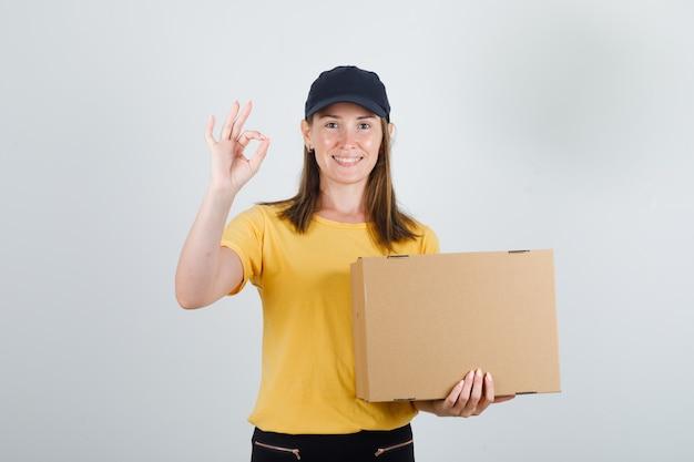 Женский курьер держит картонную коробку с футболкой, штанами, кепкой и выглядит радостно