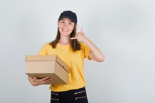 Tシャツ、ズボン、帽子で電話ジェスチャーと段ボール箱を保持し、嬉しそうに見える女性の宅配便