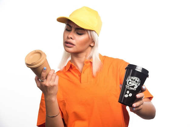 Corriere femminile che tiene e che esamina due tazze di caffè su fondo bianco. foto di alta qualità