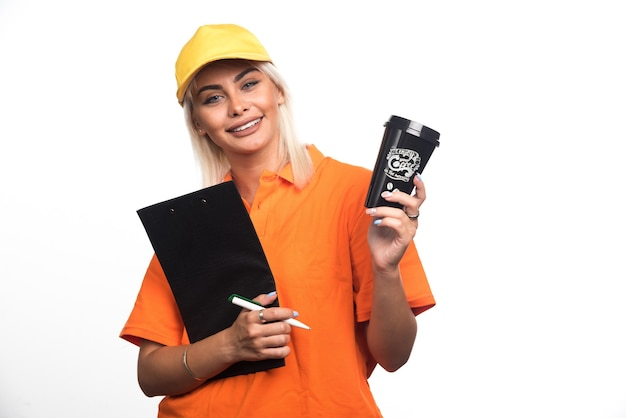 Женский курьер держит ноутбук и раздает чашку кофе на белом фоне. фото высокого качества