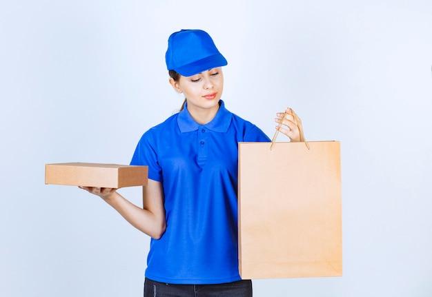 白い背景のペーパークラフトボックスで注文を保持している女性の宅配便。