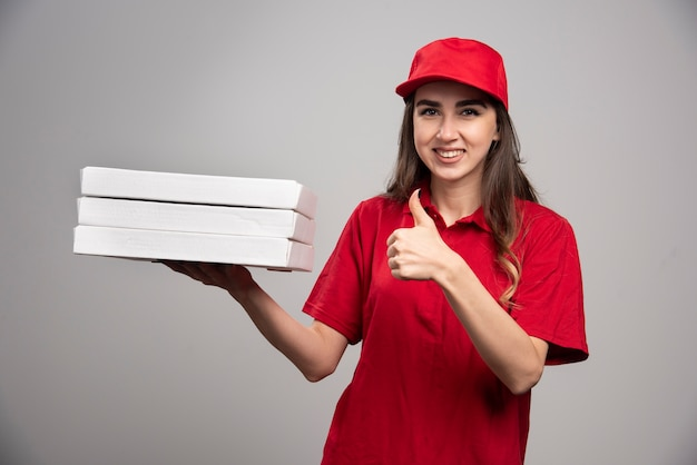 Female courier holding pizza boxes and giving thumbs up.