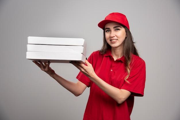 Corriere femminile che tiene le scatole per pizza sul muro grigio.