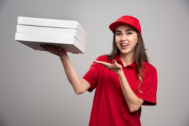 Female courier holding pizza boxes on gray wall.