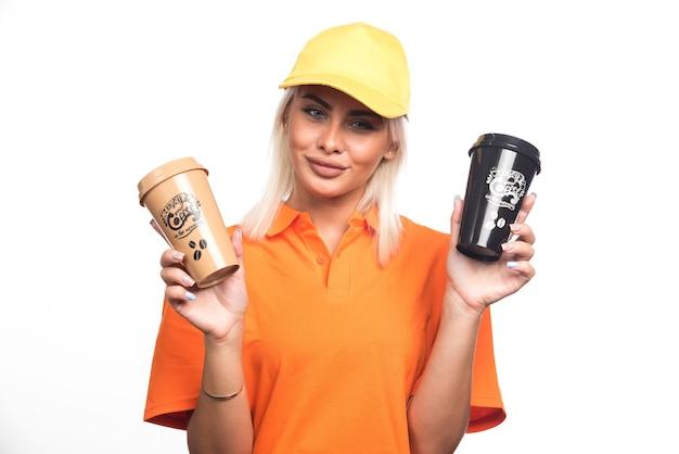 Corriere femminile che tiene due tazze di caffè su fondo bianco. foto di alta qualità
