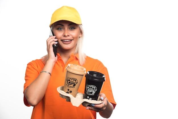 Corriere femminile che tiene due tazze di caffè su fondo bianco mentre parla con il telefono. foto di alta qualità Foto Gratuite