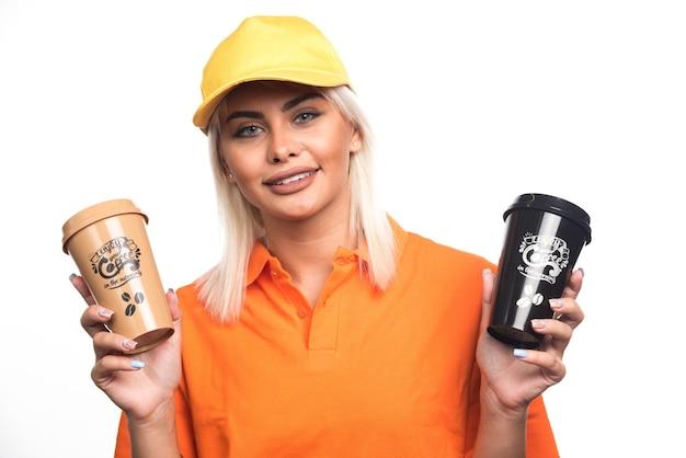 Женский курьер, держа две чашки кофе на белом фоне. фото высокого качества