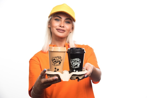 Женский курьер, держа две чашки кофе на белом фоне, улыбаясь. фото высокого качества