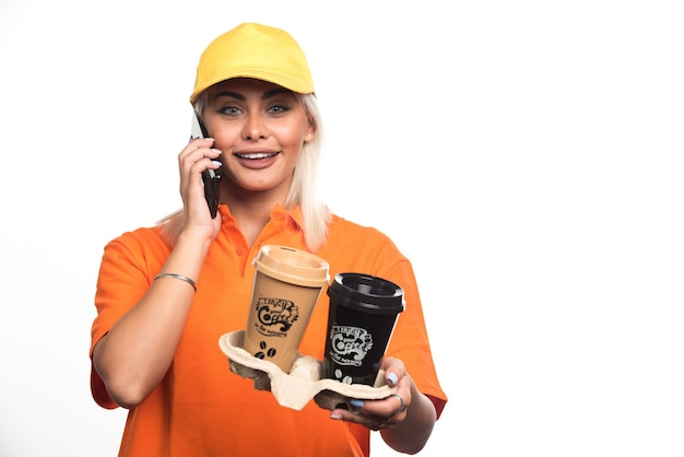 Женский курьер держит две чашки кофе на белом фоне во время разговора по телефону. фото высокого качества