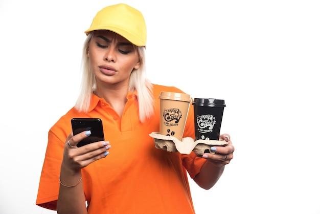 Женский курьер держит две чашки кофе на белом фоне при использовании телефона. фото высокого качества