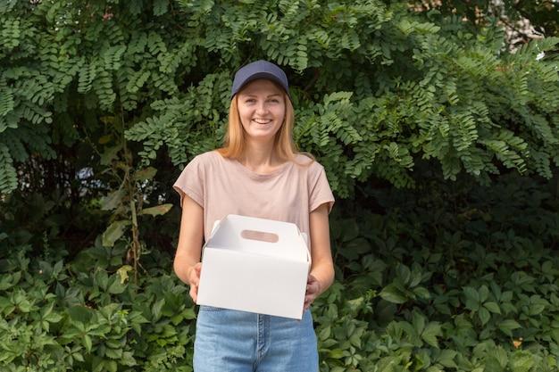マークのない段ボール箱にデザートを保持している青い帽子の女性宅配便。配信サービスのコンセプトです。広告エリア。