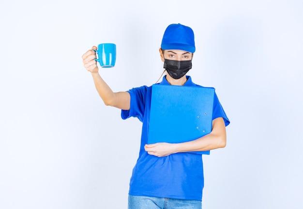 Курьер-женщина в синей форме и черной маске держит синюю папку и делится чашкой чая со своим коллегой.