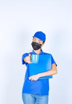 파란색 유니폼과 검은색 얼굴 마스크를 쓴 여성 택배사는 파란색 폴더를 들고 동료와 차 한 잔을 공유합니다.