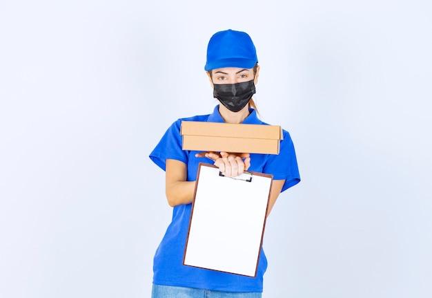 青いユニフォームとフェイスマスクを身に着けた女性の宅配便業者が段ボールの小包を配達し、顧客に空白に署名するように求めます。