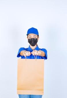 青いユニフォームとフェイスマスクの女性の宅配便は、顧客に段ボールの買い物袋を届けます。