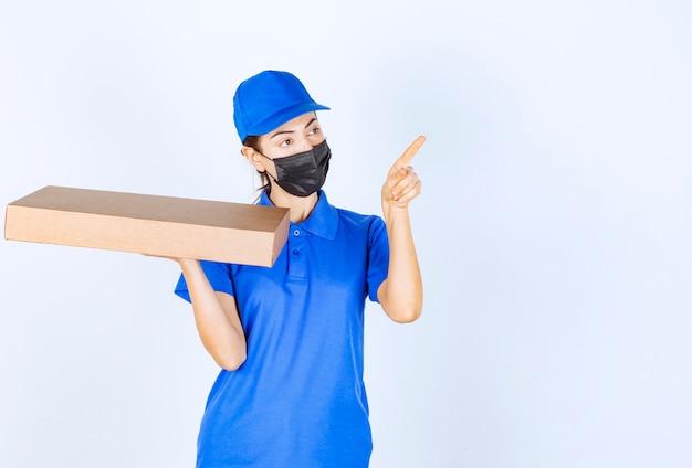 Женский курьер в синей форме и маске держит картонную коробку и указывает куда-то.