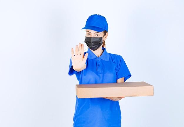 Женский курьер в синей форме и маске держит картонную коробку и что-то останавливает.