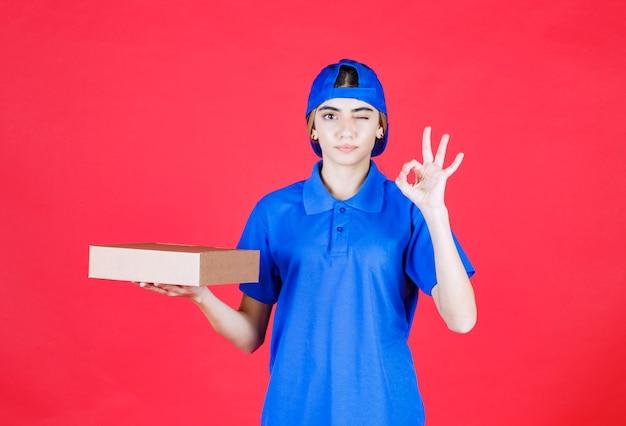 파란색 유니폼 골 판지 상자를 들고 즐거움 기호를 보여주는 여성 택배.