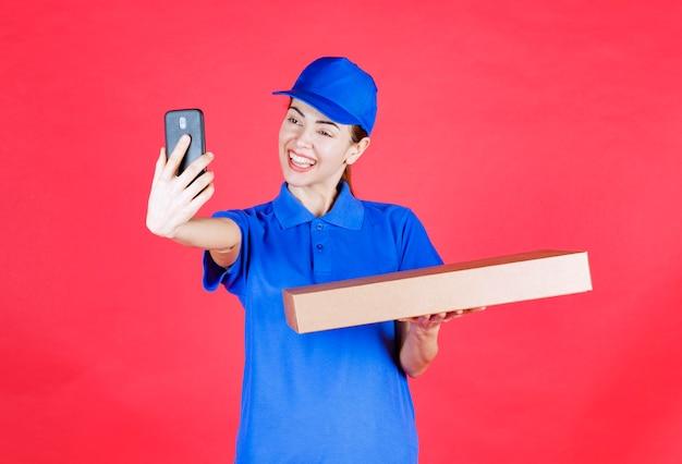 Женский курьер в синей форме держит картонную коробку для пиццы на вынос и принимает ее селфи.