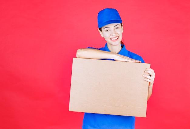 마분지 테이크아웃 피자 상자를 들고 파란색 제복을 입은 여성 택배.