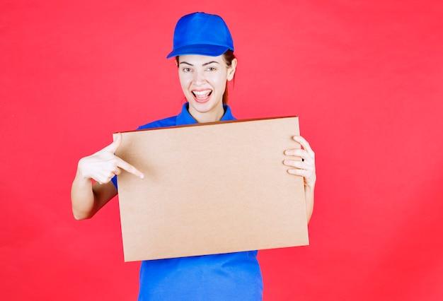 Женский курьер в синей форме держит картонную коробку для пиццы на вынос.
