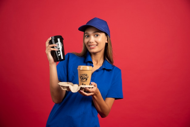 2つのカップのカートンを保持している青い制服を着た女性の宅配便。