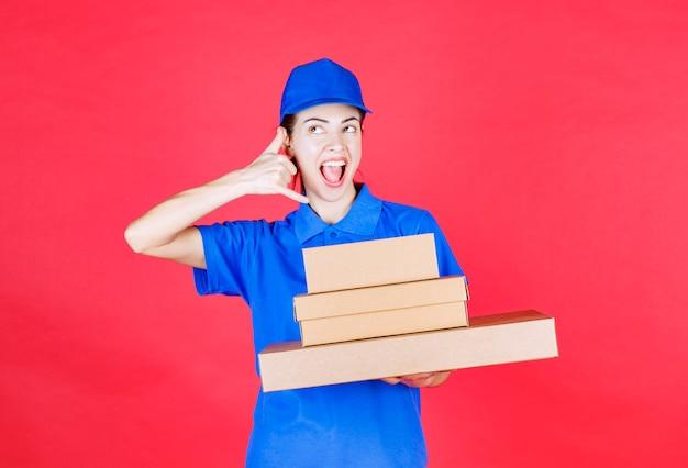 段ボール箱の在庫を保持し、電話を求める青い制服を着た女性の宅配便。 無料写真