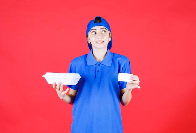 白い持ち帰り用の箱と名刺を持っている青い制服を着た女性の宅配便は、思慮深く見えます。