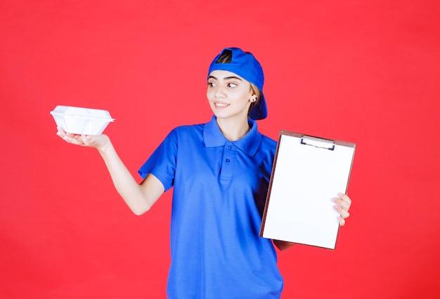 白いテイクアウトボックスを保持し、署名のチェックリストを提示する青い制服を着た女性の宅配便