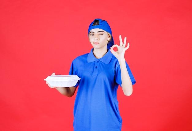 白いテイクアウトボックスを保持し、楽しみの手のサインを示す青い制服を着た女性の宅配便。