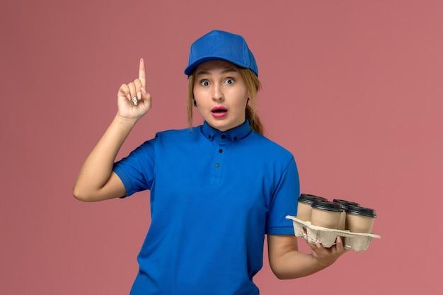 ピンクの上げられた指でポーズをとるコーヒーの茶色の配達カップを保持している青い制服の女性の宅配便、サービス制服配達