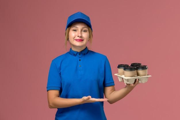 ピンクの微笑みを浮かべて茶色のコーヒーの配達カップを保持している青い制服の女性の宅配便、サービス制服配達の仕事