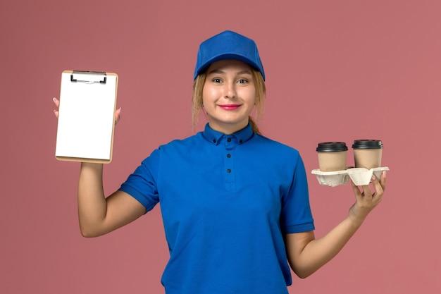 ピンクのコーヒーとメモ帳の配達カップを保持している青い制服の女性の宅配便、サービス労働者の制服の配達