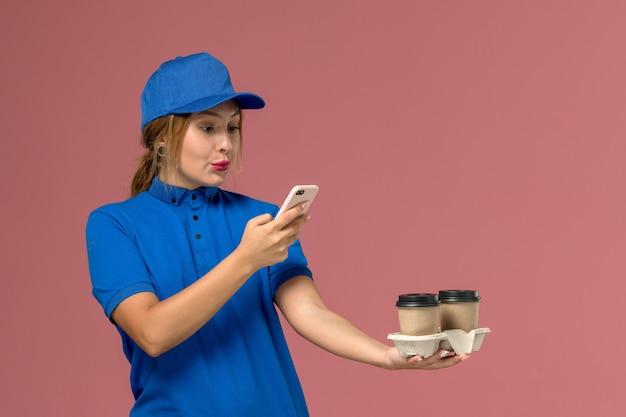 コーヒーの配達カップを保持し、ピンクのサービスジョブ制服配達で彼女の電話を使用して青い制服を着た女性の宅配便