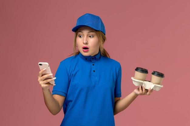 Женщина-курьер в синей форме держит доставочные чашки кофе и использует свой телефон с шокированным выражением лица на розовом, служба доставки униформы