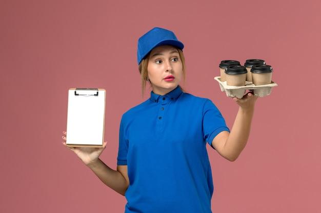 Женщина-курьер в синей форме держит блокнот вместе с коричневыми чашками кофе на светло-розовом, доставка униформы службы работы