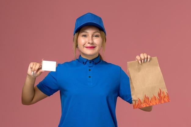 淡いピンクの白いカードと食品パッケージを保持している青い制服の女性の宅配便、サービス制服配達の仕事