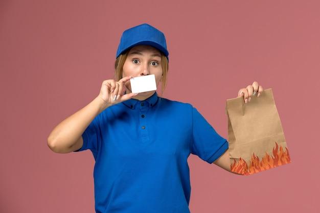 Женщина-курьер в синей форме держит белую пластиковую карточку с продуктовым пакетом на розовом, работа по доставке формы службы