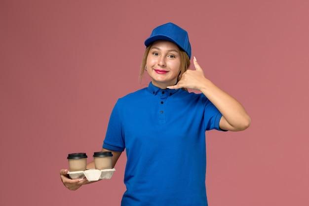 ピンクの電話ジェスチャーを示すコーヒーのカップをポーズと保持している青い制服を着た女性の宅配便、サービス制服の配達の仕事