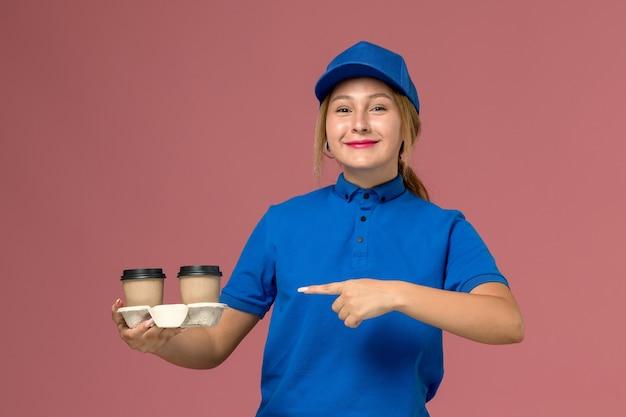 青い制服を着た女性の宅配便は、ピンクの笑顔でコーヒーのカップをポーズし、保持し、サービス制服の配達の仕事