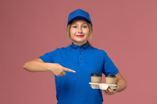 ピンクの微笑みを浮かべてコーヒーのカップを保持している青い制服ポーズの女性の宅配便、サービス制服配達労働者