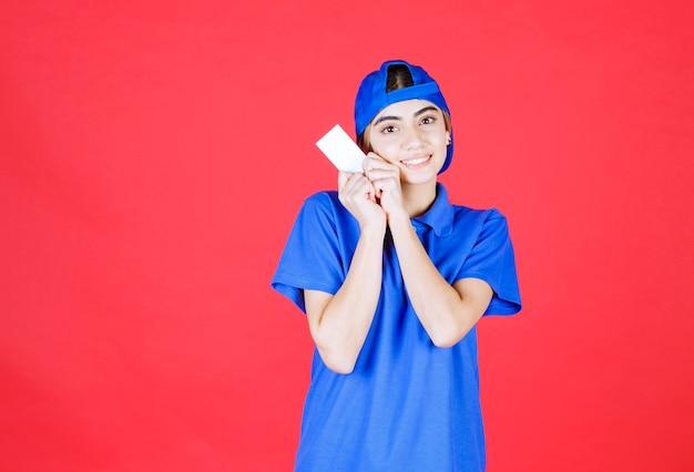 Женский курьер в синей форме представляет свою визитную карточку и чувствует себя счастливее.